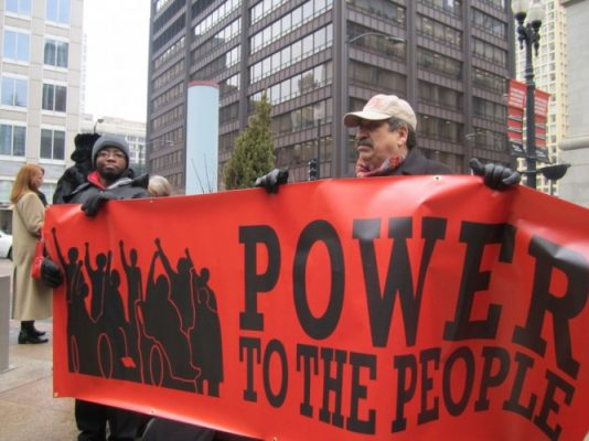 "Image of people with disabilities holding a red banner that reads ""power to the people"""
