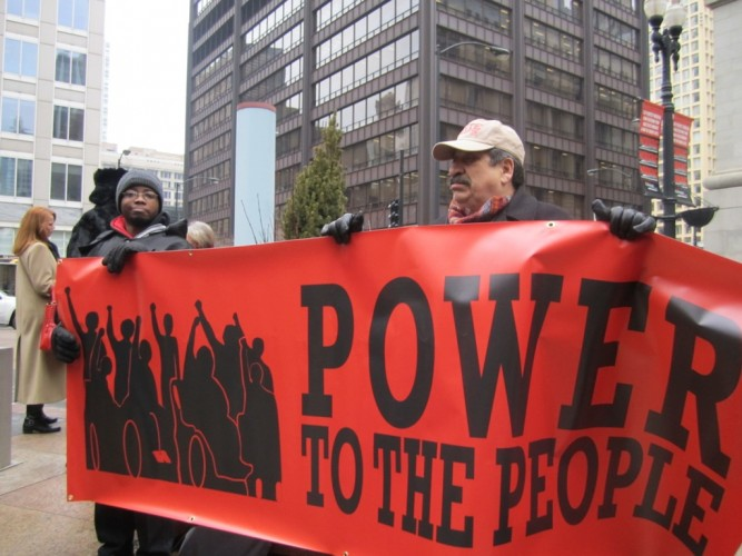 """Image of people with disabilities holding a red banner that reads """"power to the people"""""""