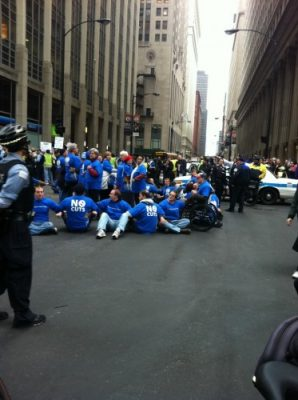 a group of people wearing blue blocked the street at Jackson and LaSalle. Also in the photo, a police officer watches