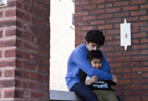 Alejandro Jaime's younger brother and cousin share a hug outside the family's home. (Photo credit: Sophia Nahli)