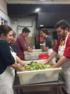 Soup kitchen volunteers prep salad for friday night food service